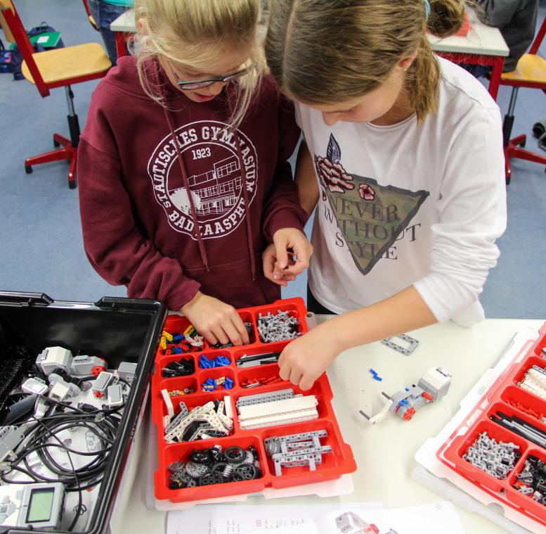 2 Mädchen bauen einen Lego-Roboter und suchen in einer Kiste nach passenden Steinen.