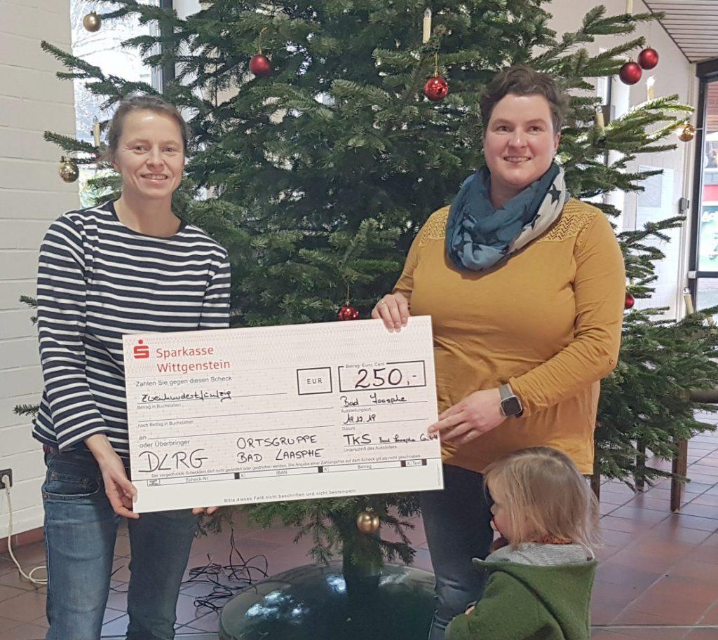 Zwei Frauen vor geschmücktem Tannenbaum mit überdimensioniertem Scheck in der Hand, der die Summe von 250 Euro ausweist.