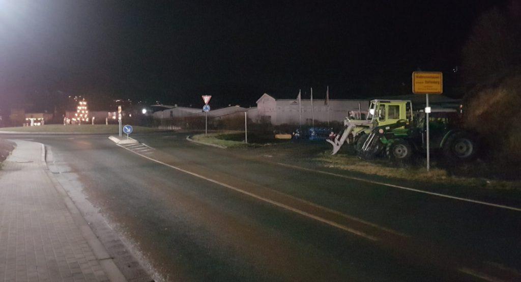 Kreisel bei Niedereisenhausen, rechts das Ortseingangsschild, davor geparkte Traktoren eines benachbarten Fachgeschäfts. Es ist dunkel.