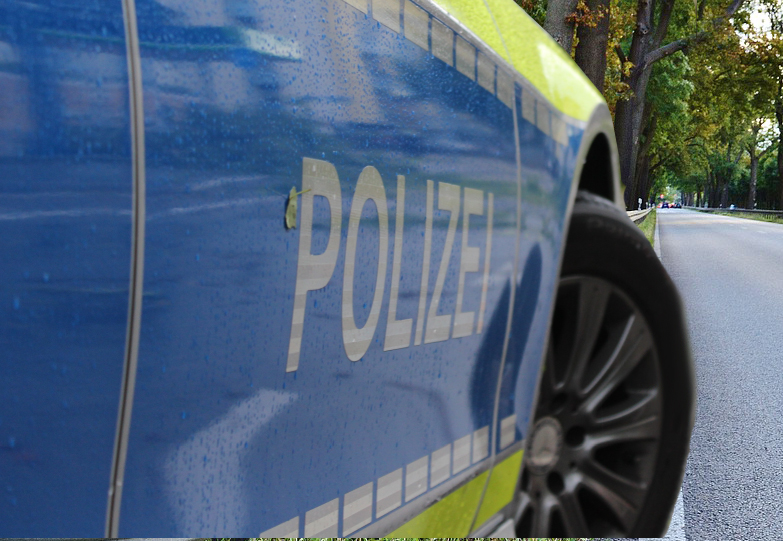 Ein Polizeifahrzeug (nur der untere Frontbereich ist zu sehen) steht an der Seite einer mit Bäumen gesäumten Bundesstraße. Symbolisch für die B 253 bei Breidenbach wo die Straßensperrung in der Nacht stattfand.