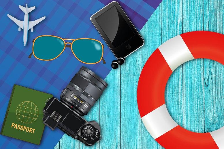Eine Grafik, die Urlaub assoziiert. EIne Kamera, eine Sonnenbrille, ein Schwimmreifen, ein Flugzeugsymbol... alles auf einem blauen Untergrund der den Eindruck von Handtuch und Badesteg erweckt.