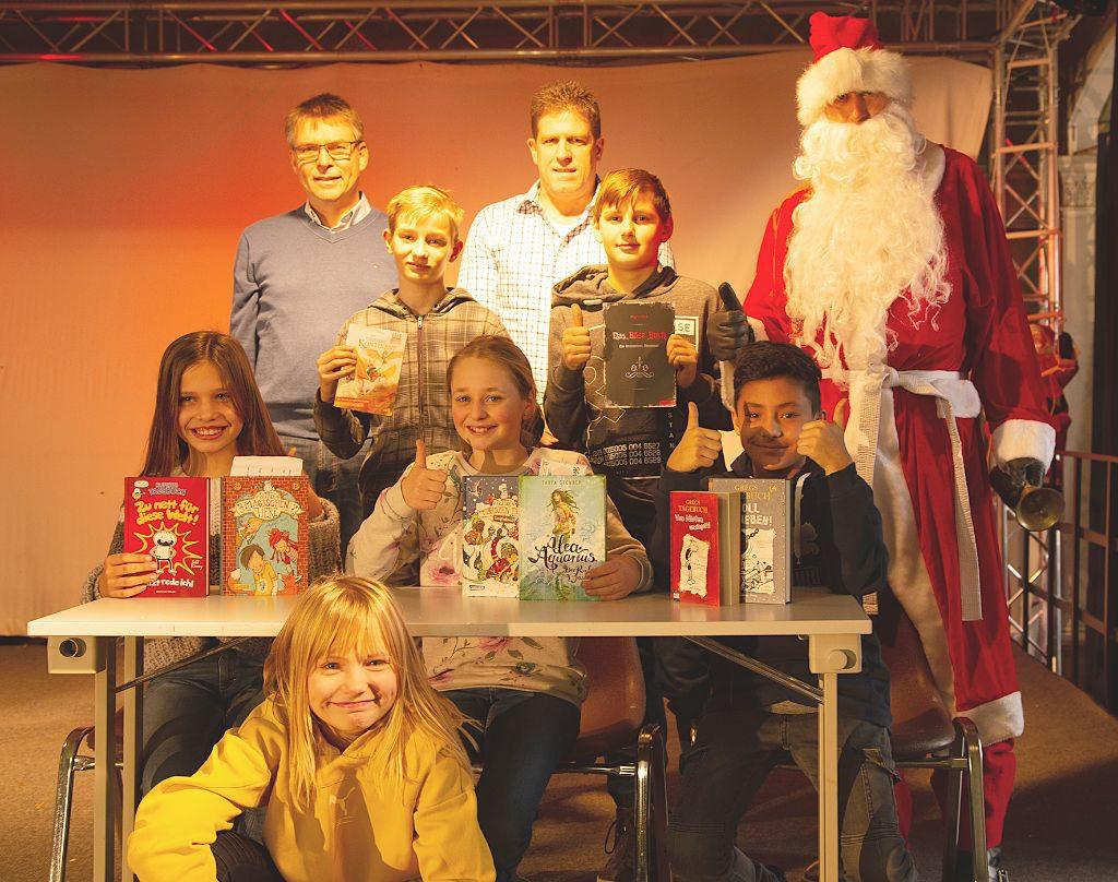 Die fröhlichen Sieger des Vorlesewettbewerbs (dre Mädchen und drei Jungs) mit zwei Lehrern und dem Nikolaus beim Gruppenfoto