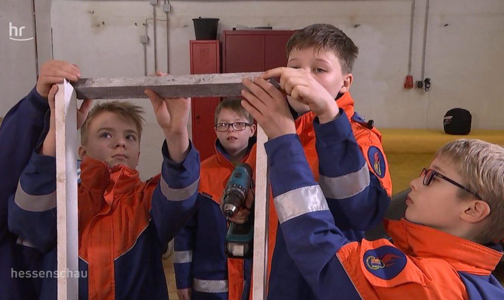 Vier Jungen aus der Jugendfeuerwehr Weifenbach bauen eine Seifenkiste zusammen. Sie tragen Jugendfeuerwehr-Uniformen.