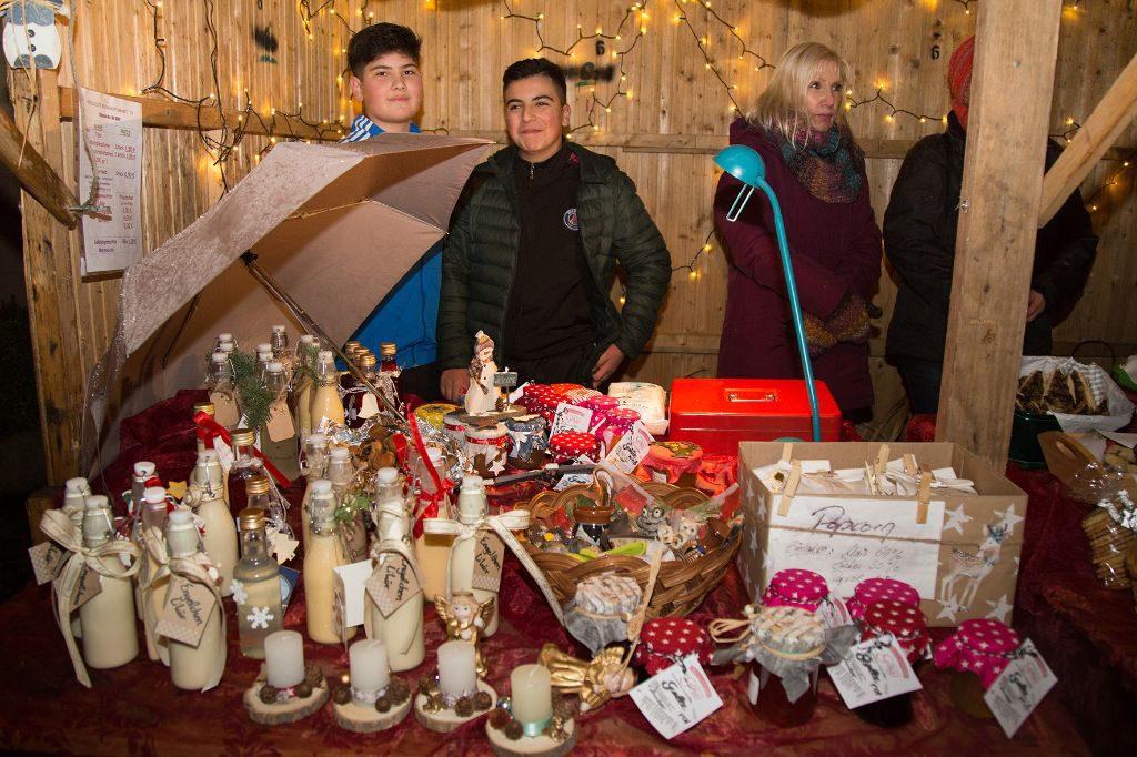 Zwei Jungs stehen vor einem Stand mit liebevoll dekorierten Geschenkartikeln - Flaschen, Kerzen und Konfitüren.