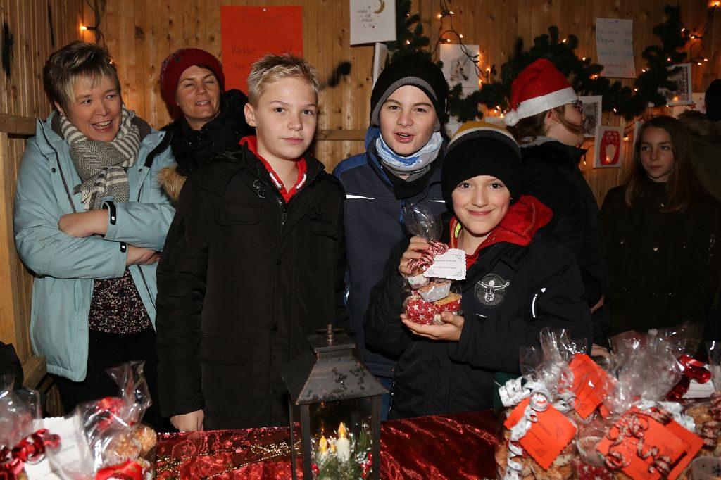 Schüler an einem Stand des Weihnachtsmarkts. Sie bieten Lose für die Tombola an.