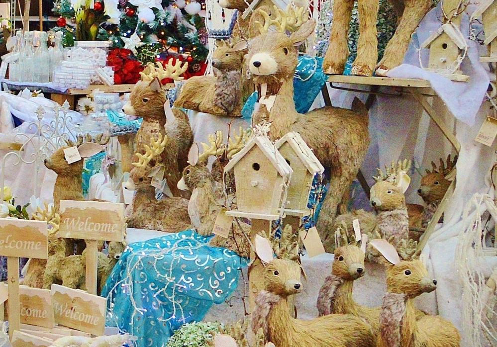 Gebastelte Vogelhäuschen, Rentiere, Weihnachtsbaumschmuck, dekorierte Flaschen... schöne weihnachtliche Waren sind zum Verkauf drapiert.