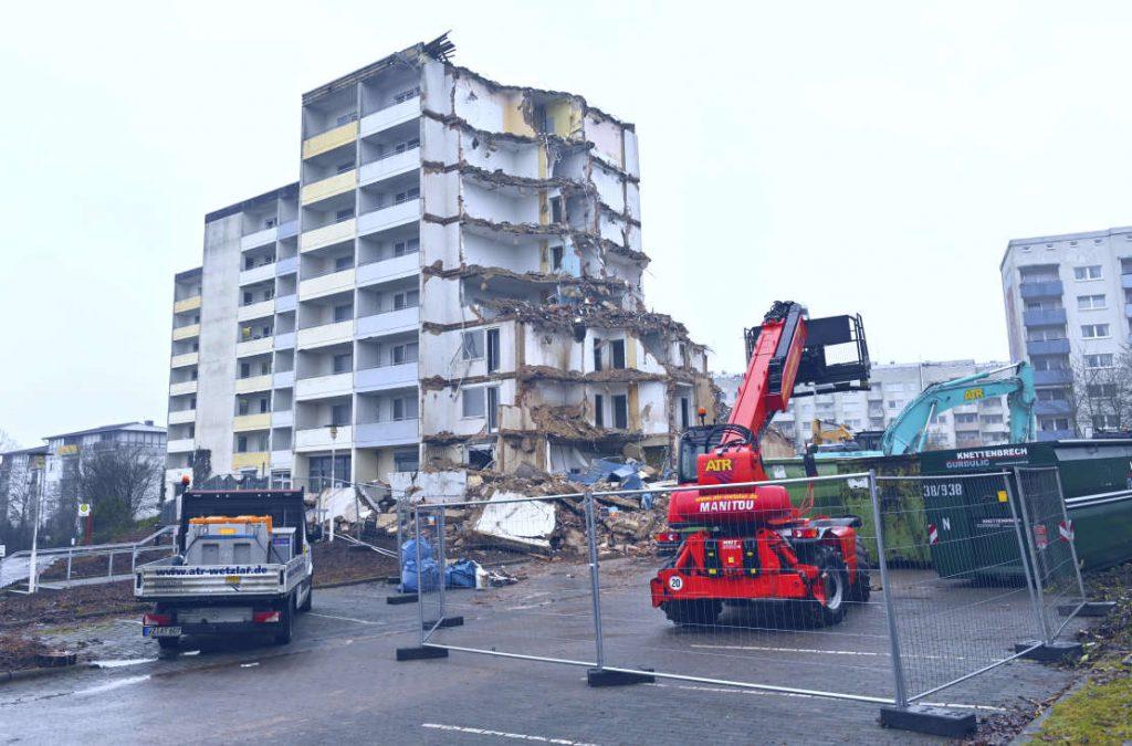 Siebenstöckiges Gebäude. Teils abgerissen. Trümmer und Bagger davor. Bauzaun im unteren Bildbereich.