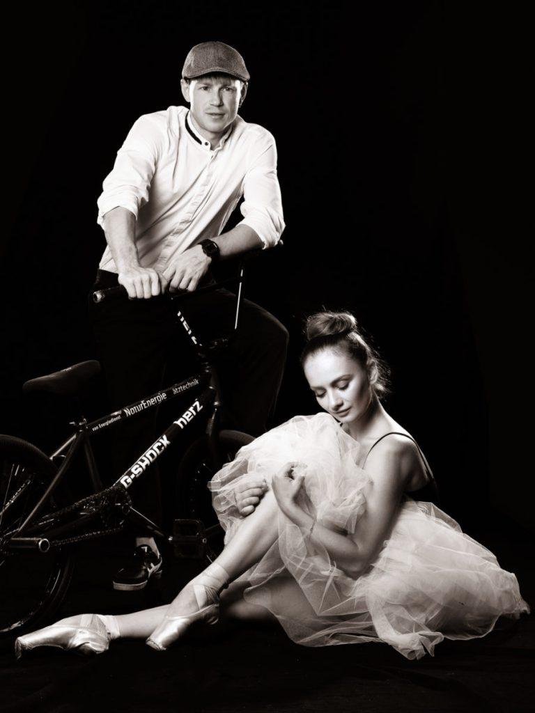 Ein BMX-Radler mit Rad und davor sitzend eine Ballerina im Tütü