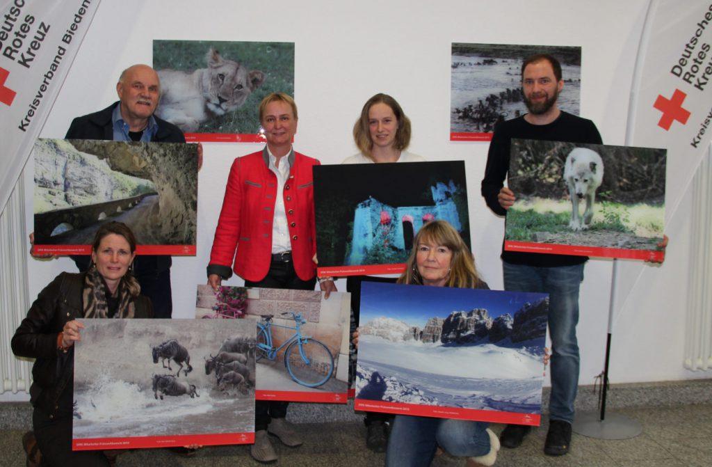Sechs Preisträger mit je einem großformatigen Foto in der Hand stellen sich zum Gruppenfoto auf. Im Hintergrund zwei weitere Aufnahmen an der Wand.