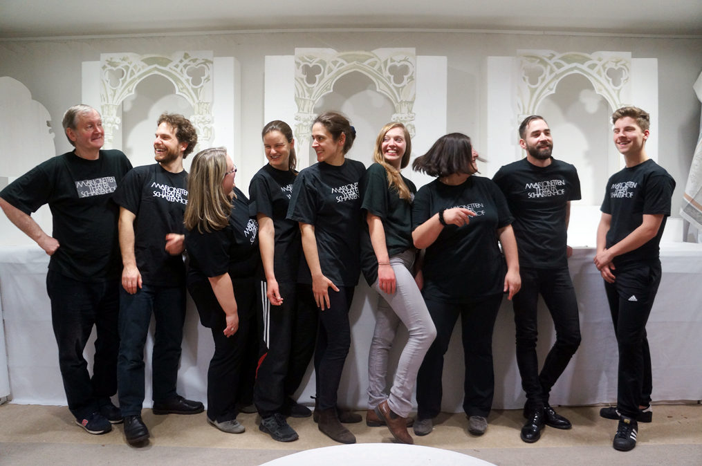 Das neunköpfige Team der Marionettenspieler. Alle in schwarzen Hosen und schwarzem T-Shirt.