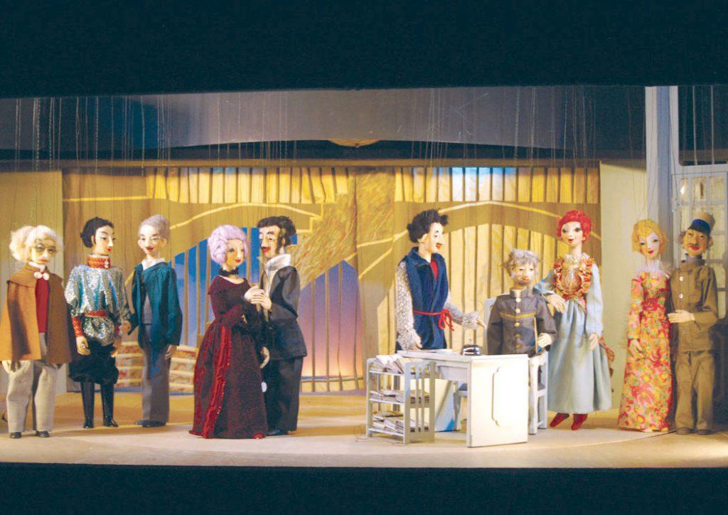 """Zehn kostümierte Marionetten auf der kleinen Marionettenbühne. Zwei Figuren """"tanzen""""."""