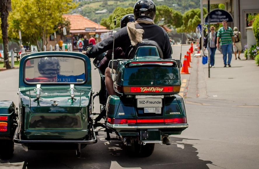 Motorrad mit Beiwagen. Große Straße mit Bäumen am Rand. Spaziergänger.