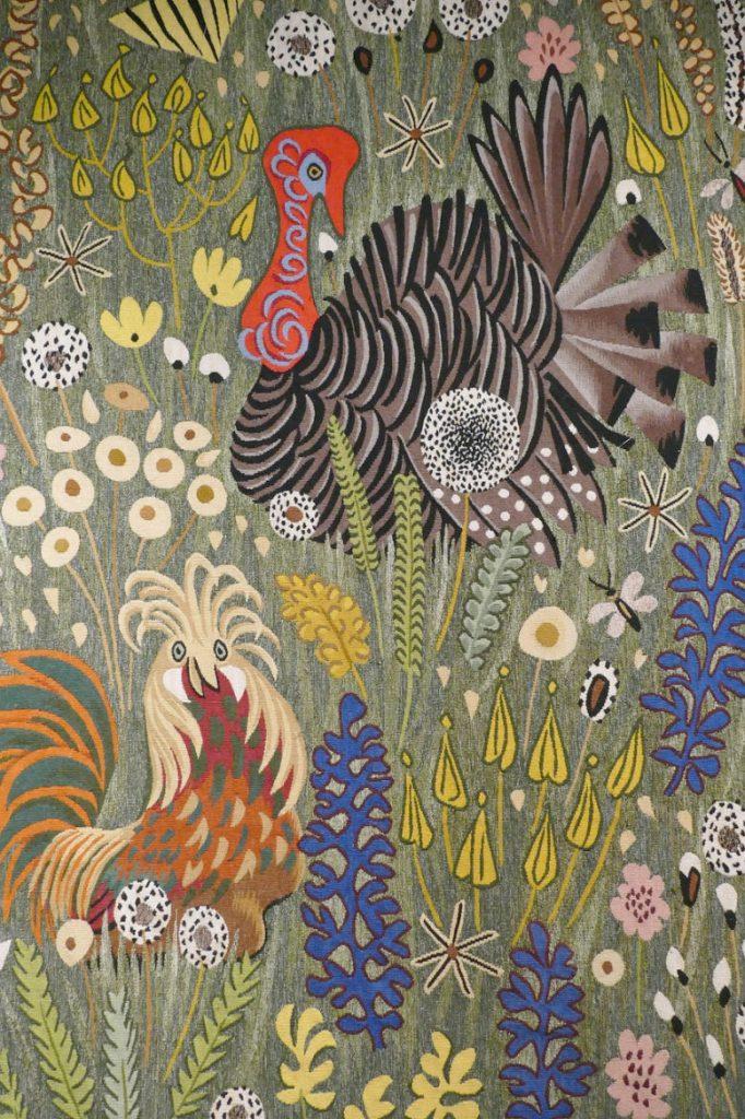Ein gesticktes Gobelin-Bild. Es zeugt einen Truthahn inmitten von Blumen, Löwenzahn und Kräutern...