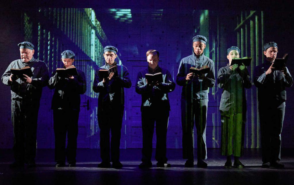 Sieben Sträflinge auf der Theaterbücher. Alle in je einem Buch lesend. Hintergrund: Knastgitter.