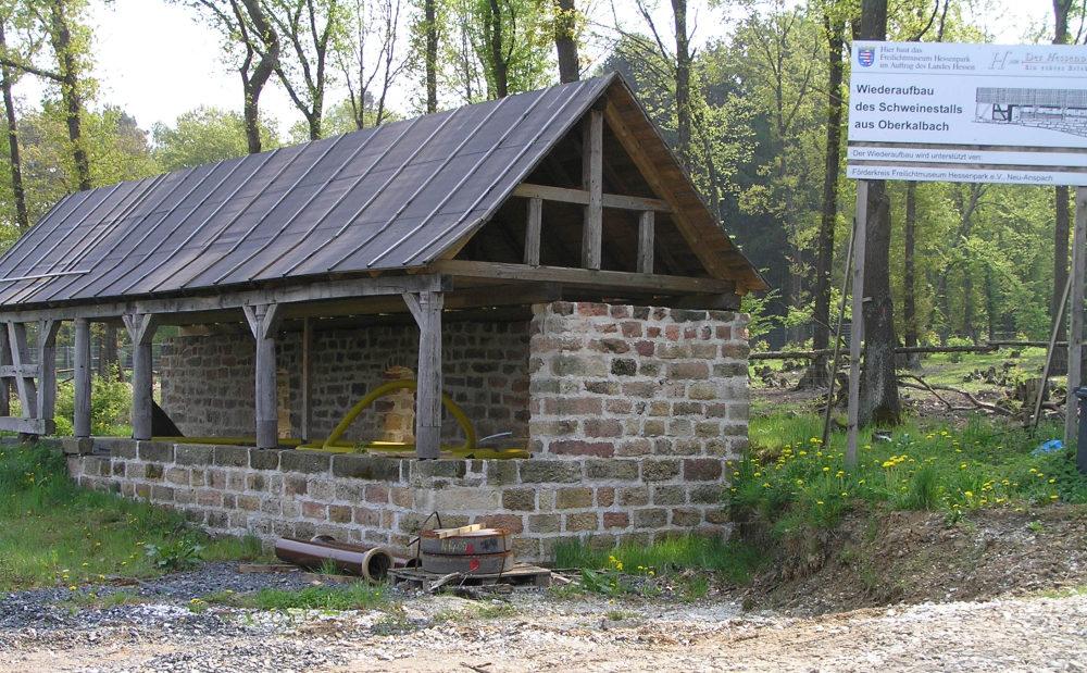 Der im Restaurieren begriffene Schweinestall im Hessenpark. Aus alten Backsteinen und Holzbalken mit einem Teerpappe-Dach.