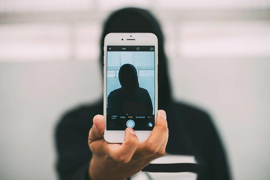 Mann, schemenhaft in dunklem Kapuzenpullover hält ein Handy vor sich.