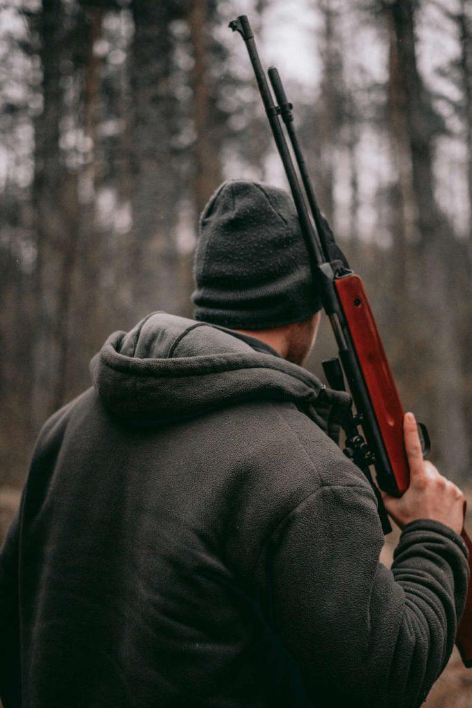 Jäger, von hinten zu sehen, mit geschultertem Gewehr im Wald.