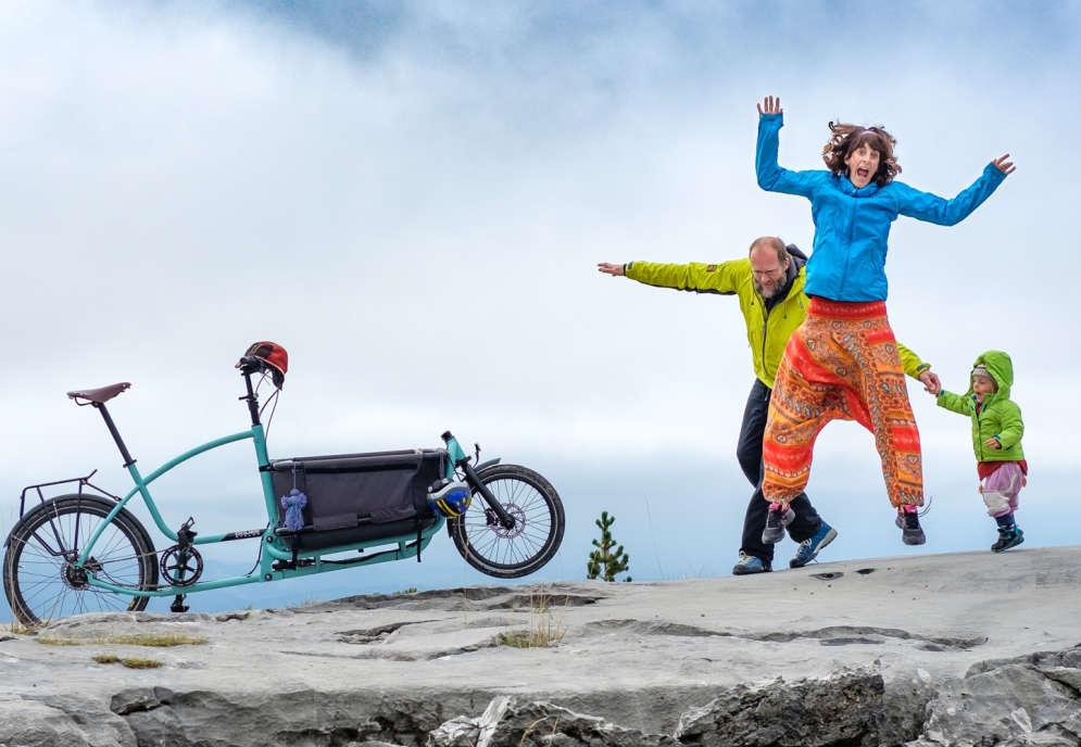 Ein Fels vor dem Meer, ein Lastenrad, eine Familie mit Vater, Mutter, Kind die fröhlich springen.