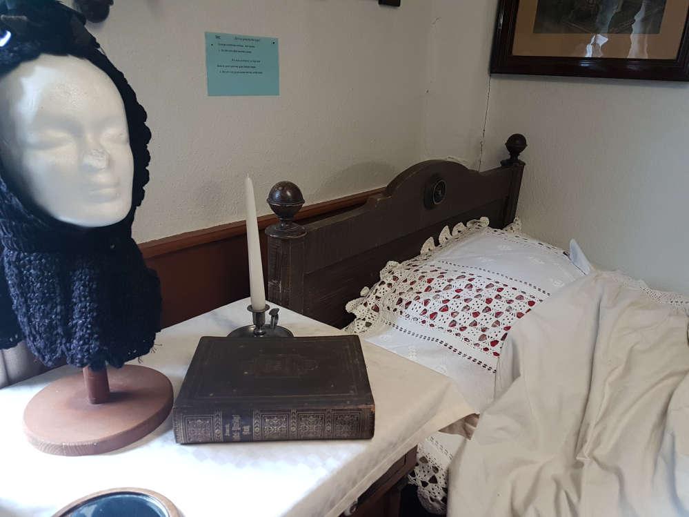 Ein Blick in ein Schlafzimmer längst vergangener Zeit. Bett mit Nachttisch, Bibel und Kerzenleuchter darauf ...