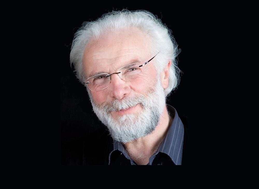 Peter Strauch. graue Haare, Vollbart, Brille. Vor schwarzem Hintergrund.