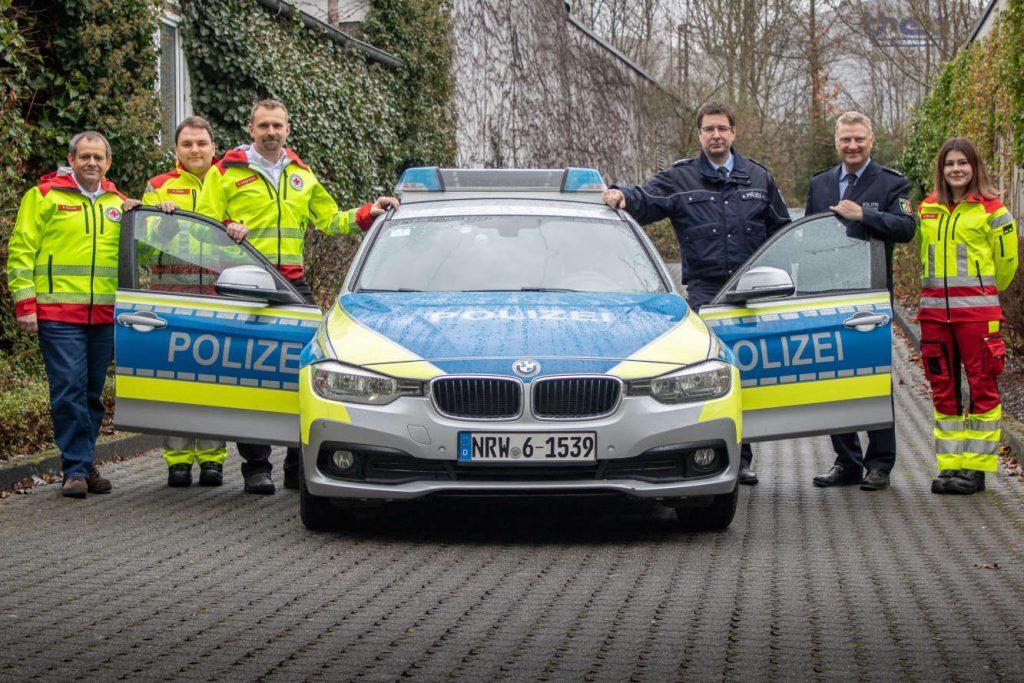 Polizeiauto mit offenen Türen. Daneben zwei Polizisten und vier Notfall-Sanitäter.