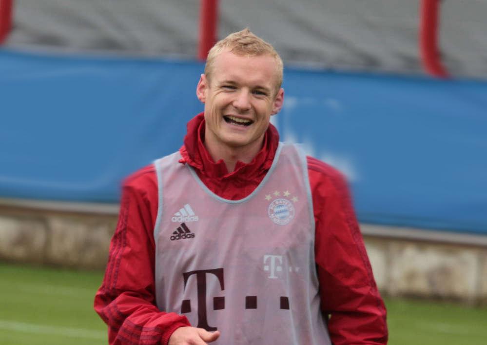 Fußballspieler Sebastian Rode. Blond, Jung. Lachend. Im Stadion.