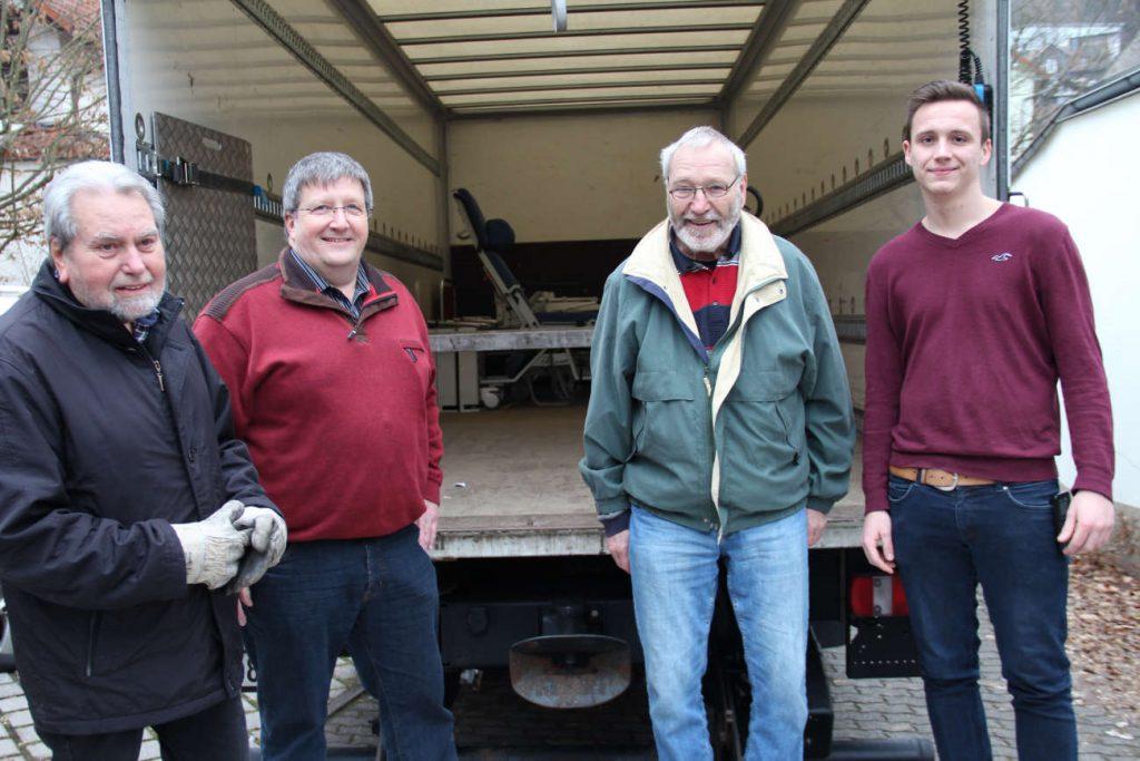 Vier Männer vor einem offenen Lkw mit dem Hilfsgüter transportiert werden sollen.