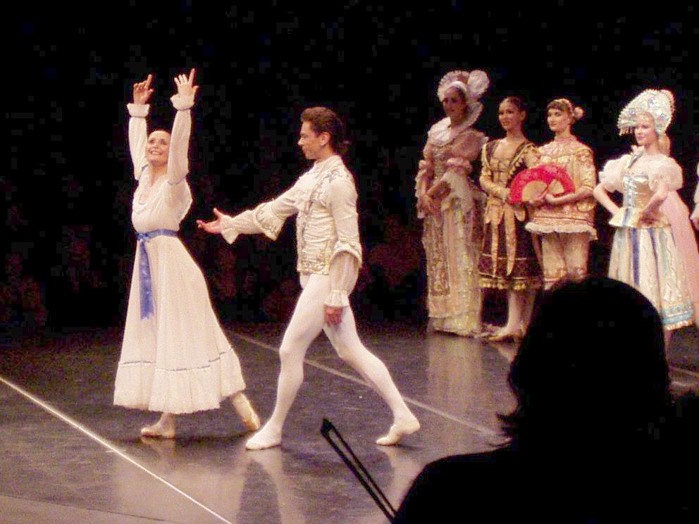 Ein Tanzpaar des St.Petersburg-Balletts agiert auf der Bühne tänzerisch im Vordergrund. Vier barock kostümierte Tänzerinnen stehen im Hintergrund und warten auf ihren Einsatz.