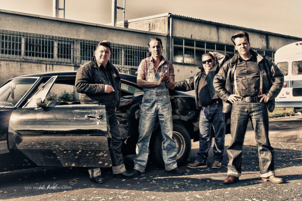 Das Foto mutet  50er Jahre-mäßig an. Vier Jungs stehen in Jeans und Hemden, teils Lederjacken an ein altes Auto gelehnt vor einem alten Fabrikgebäude.