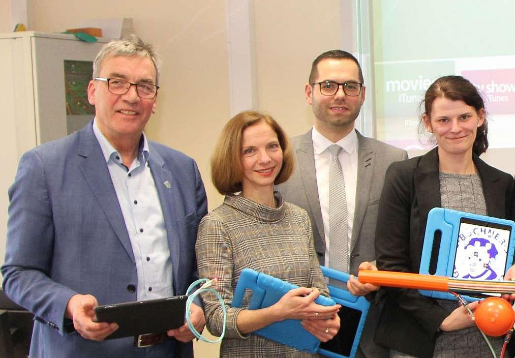 Vier offizielle Vertreter (2 Frauen und w Männer) mit Schüler-Laptops.