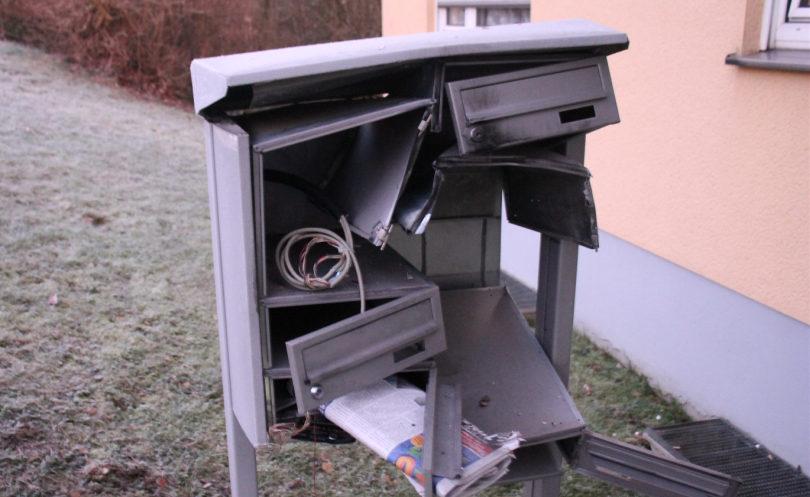 Eine zerstörte Briefkastenanlage vor einem lachsfarbig verputztem Haus. Raureif auf der Wiese.