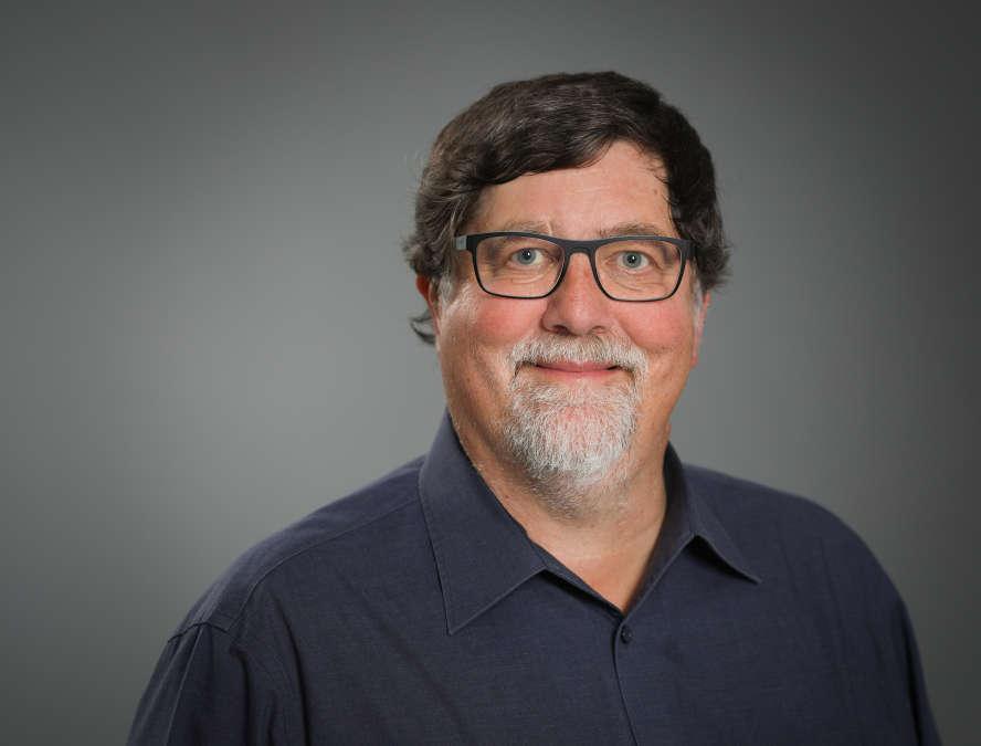 Ein Mann in schwarzem Hemd mit dunklen vollen Haaren und grauem Oberlippen- und Kinnbart.