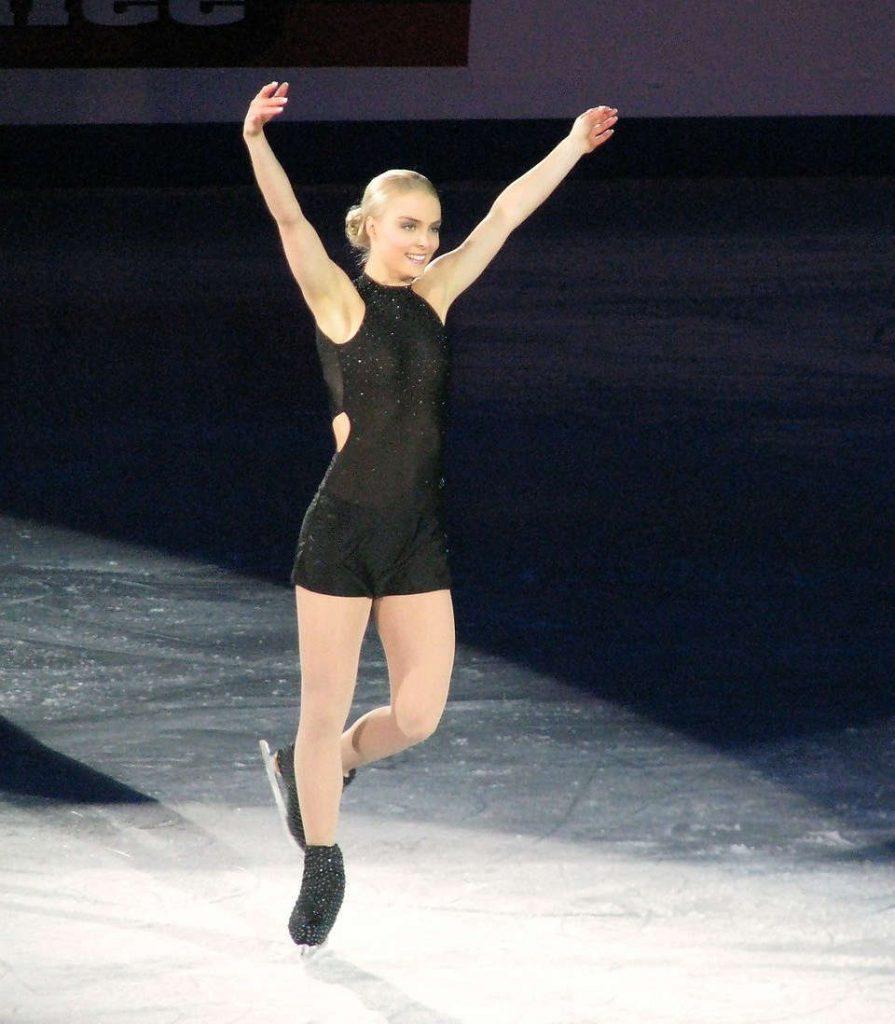 Eiskunstläuferin in schwarzem Glitzerdress auf der Eisfläche - die Arme hochgereckt.