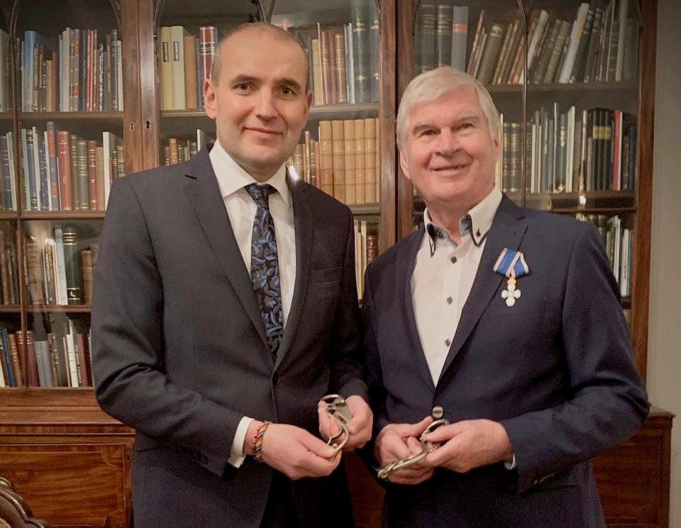 Der Träger des Falkenordens (am Revers befestigt) und der Präsident vor einem Bücherregal.