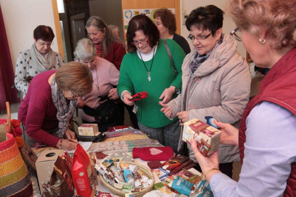 Frauen drängen sich um die Angebote herum, die auf dem Tisch des Weltladens präsentiert werden.