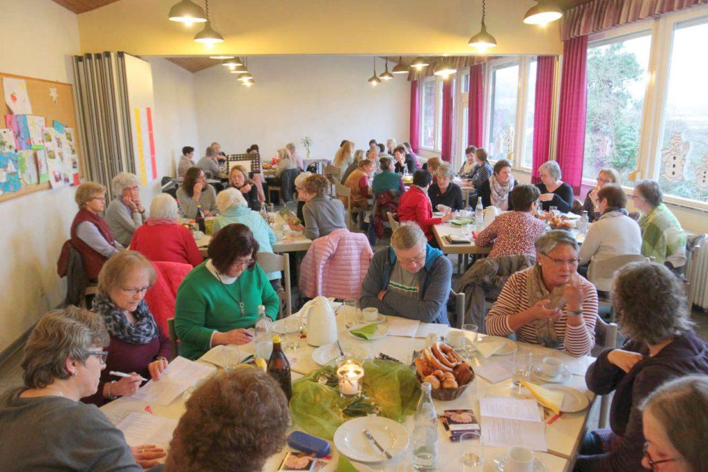 An Tischen sitzen Frauen gruppenweise und unterhalten sich angeregt.