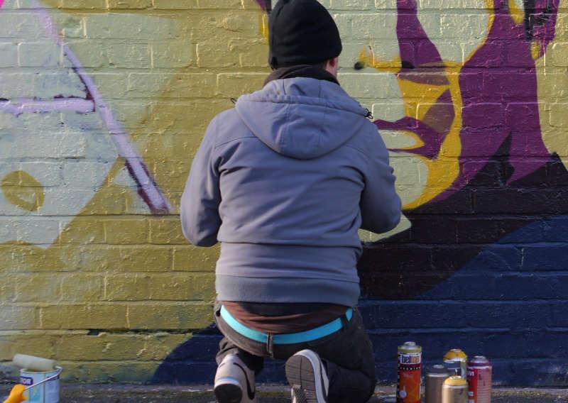 Sprayer sprüht Farbe an eine Backsteinwand.