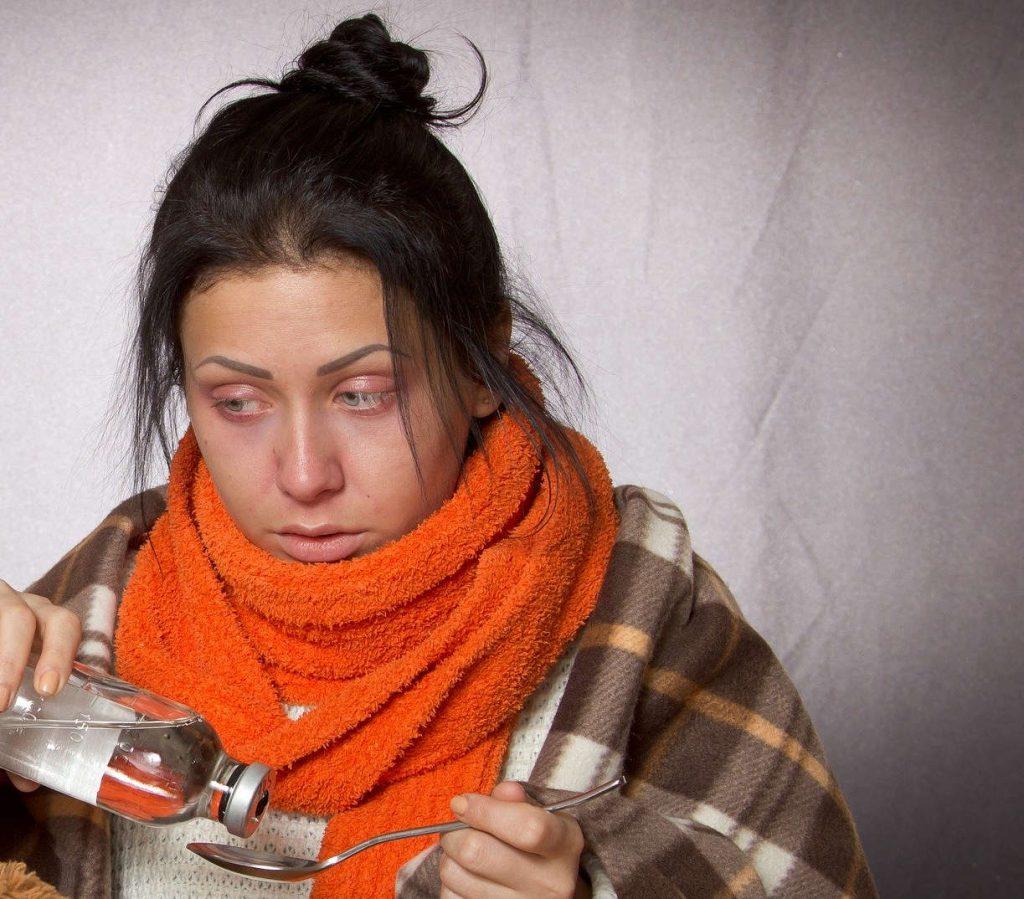 Krank wirkende Frau mit Schal um den Hals die sich ein Medikament zuführt.