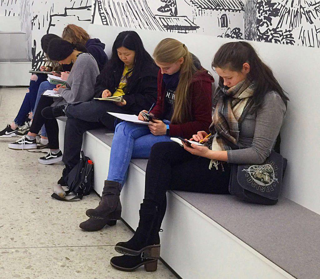5 Schülerinnen sitzen auf einer Bank in der Kunstausstellung und zeichnen konzentriert.