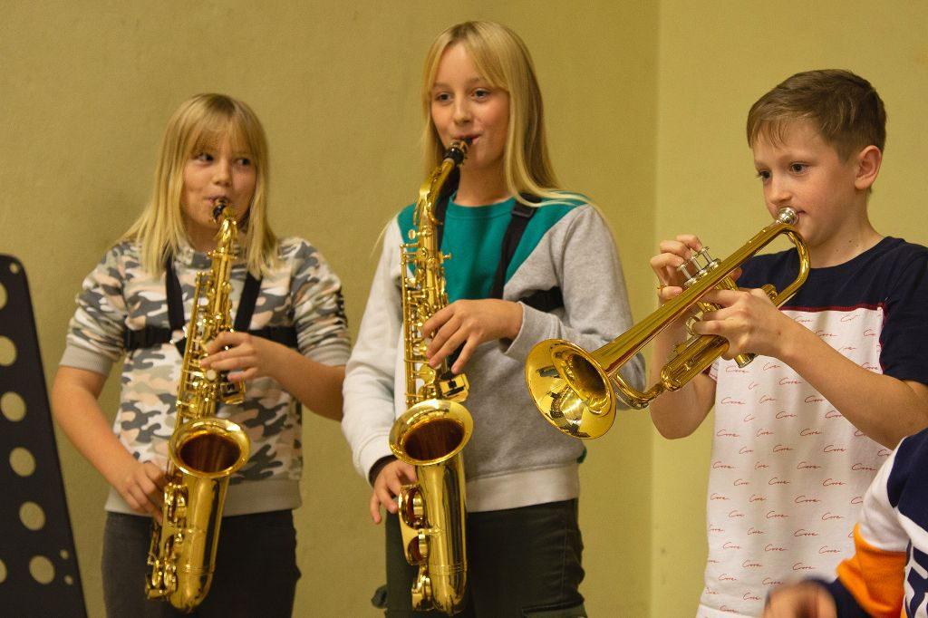 2 Mädchen mit Saxophon, 1 Junge mit Trompete spielen en Stück.