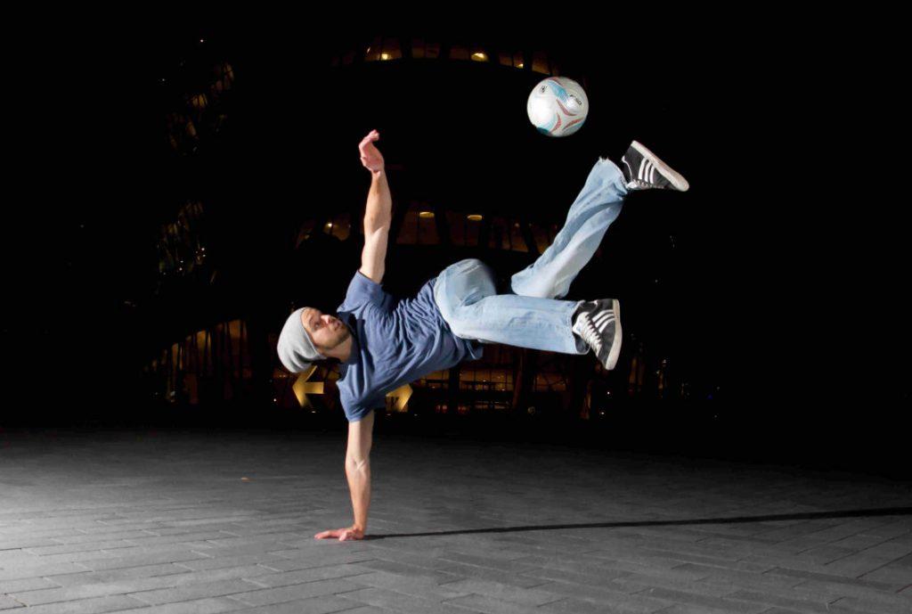 Ein Fußballartist - am Boden auf eine Hand gestützt und den Ball mit dem Fuß kickend.