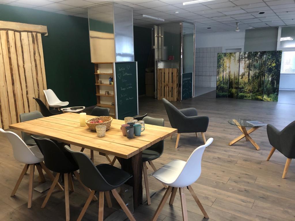 Der Raum ist mit Holztisch und schicken Sitzmöbeln gemütlich gestaltet.