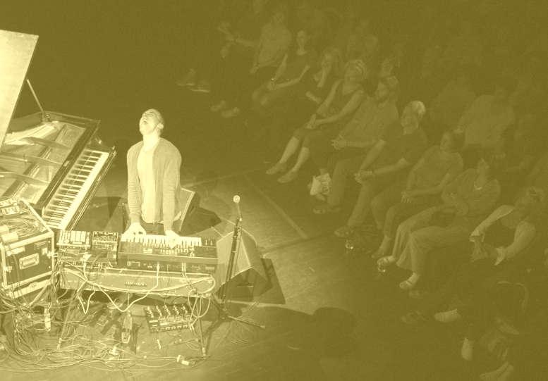 Musiker am Piano. Publikum dahinter. Schwarz-Weiß-Aufnahme.