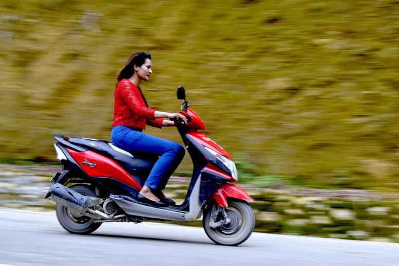 Junge Frau fährt Motorroller. In Jeans und roter Lederjacke, aber ohne Helm. Der Hintergrund ist verschwommen.
