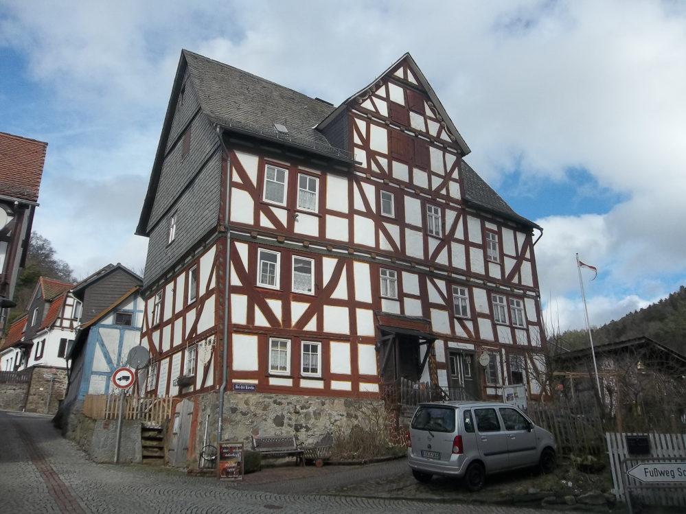 Alte Fachwerkhaus in einer Gasse, dahinter weitere Fachwerkhäuser. Giebel mit Schiefer verkleidet. kleine, weiße Sprossenfenster.