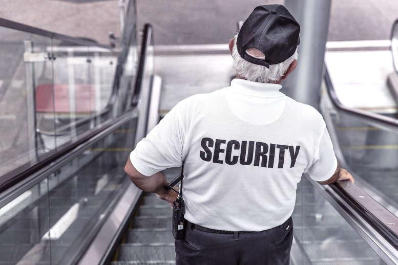 """Ein Security-Mann mit schwarzem """"Security""""-Aufdruck auf dem weißen Polohemd fährt eine Rolltreppe hinab. Sein Funkgerät hat er einstecken."""