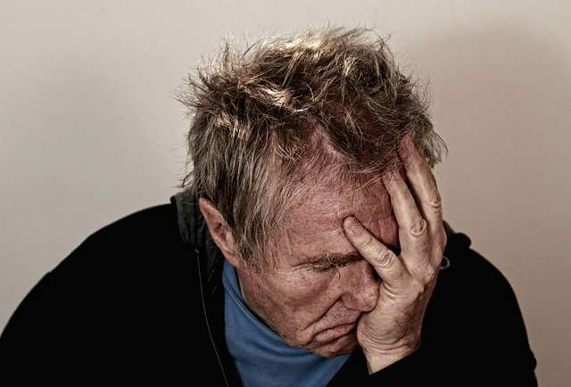 Ein scheinbar verzweifelter alter Mann der den Kopf in die Hand stützt