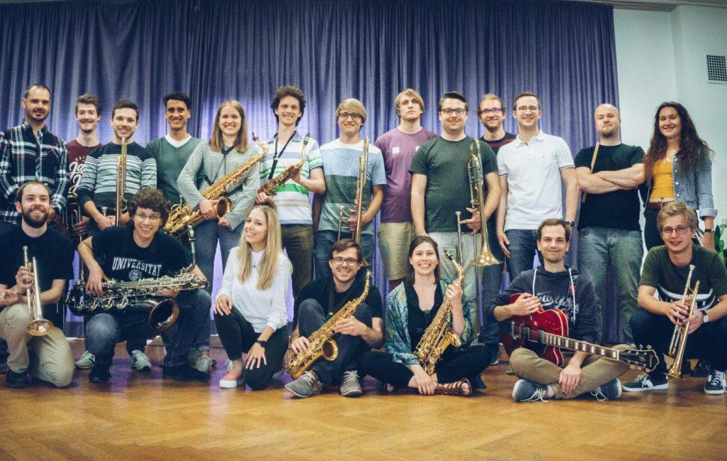 20 Studentinnen und Studenten stellen sich mit ihren Instrumenten - von Posaune bis Saxophon - zum Gruppenfoto. Die vordere Reihe hat sich gehockt.