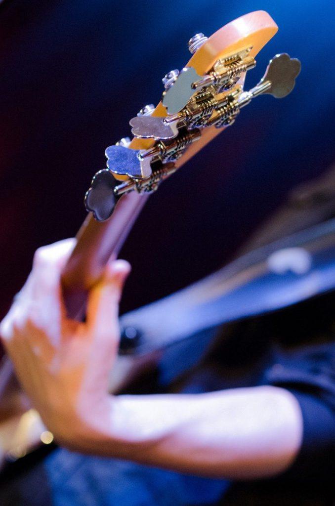 Gitarre und der Arm des Gitarristen. Mehr ist nicht zu sehen.