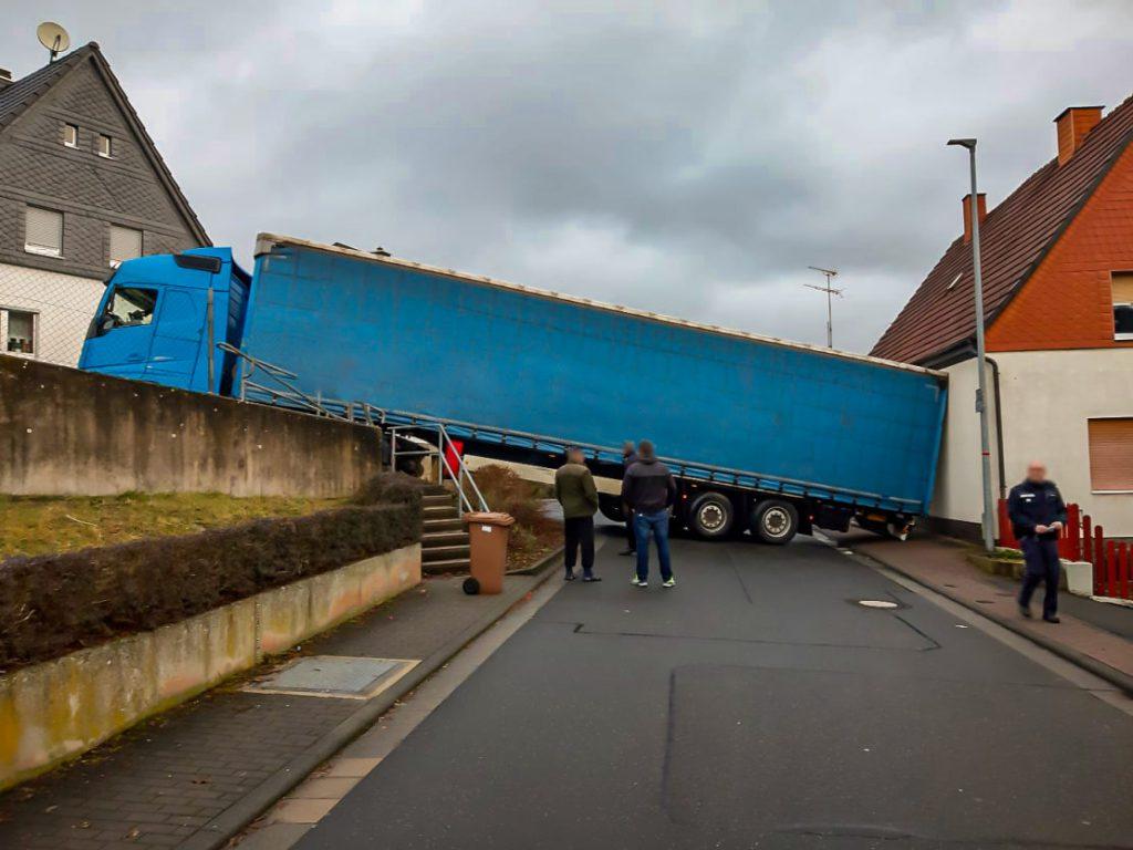 Blauer Sattelschlepper mit ebenfalls blauem Auflieger verkantet sich zwischen Straße und Wohnhaus. Nichts geht mehr.